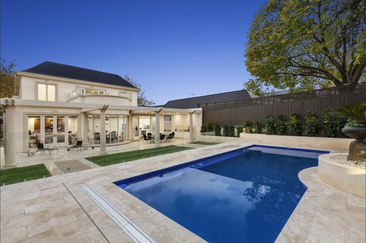 Travertine paving in beige and cream with a dark blue pool in large backyard