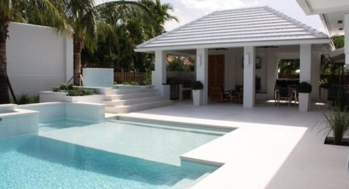 Travertine under a portico with white pool coping tiles