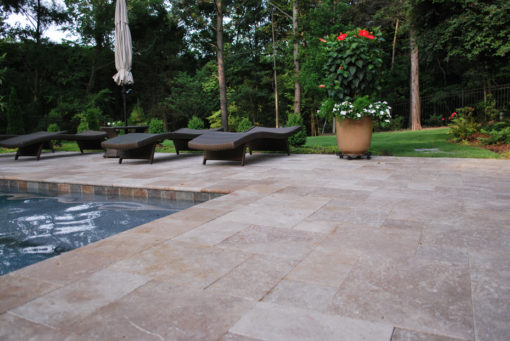 Brown pool coping tiles with surrounding pool paving on a tiles pool